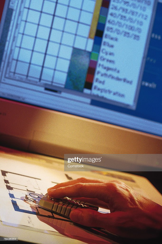 Man using four button cursor on graphics tablet : Stockfoto