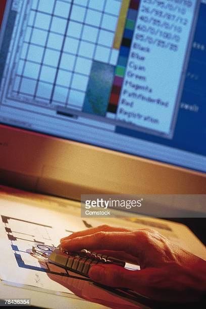Man using four button cursor on graphics tablet