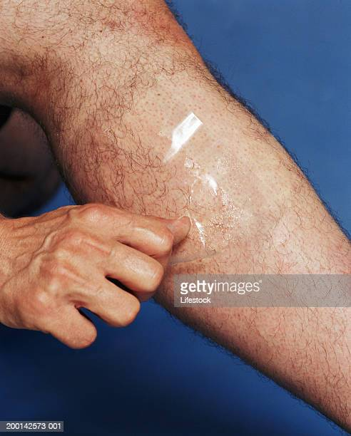 man using hair removal on legs, low section, close up - homme poilu photos et images de collection