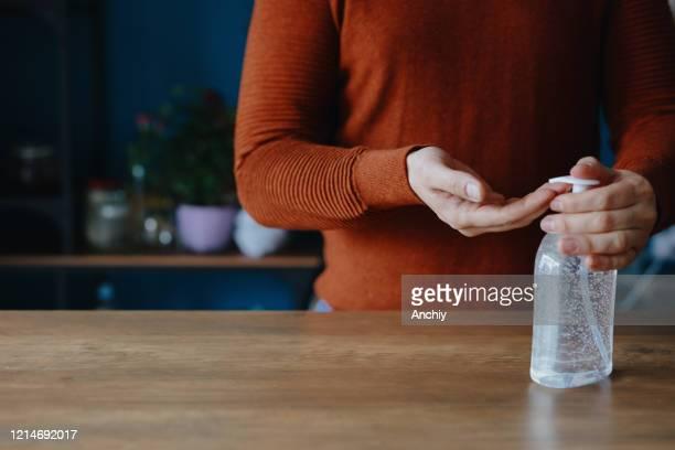 mens die handontsmettingsmiddel gebruikt om zijn handen schoon te maken - hand sanitizer stockfoto's en -beelden