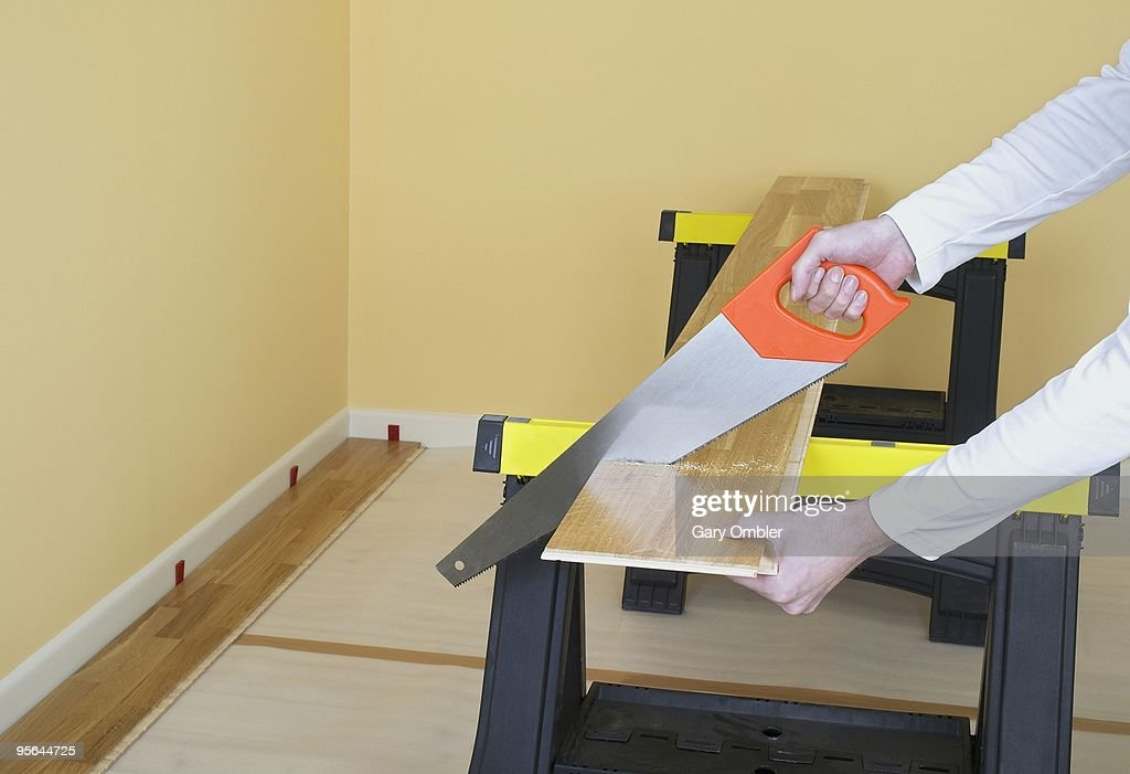 Man Using Hand Saw To Cut Through Piece Of Laminate Flooring On Workbench Stock Photo