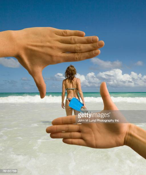man using hands to frame woman on beach - ammirazione foto e immagini stock