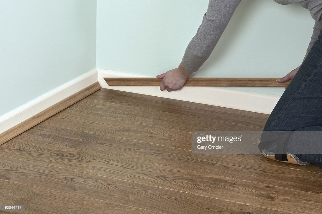 Man Using Hands To Position Edging Bead At Edge Of