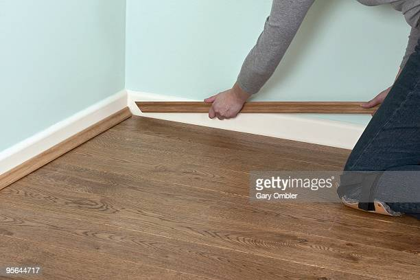 man using hands to position edging bead at edge of laminate floor and skirting board - wainscoting stock photos and pictures