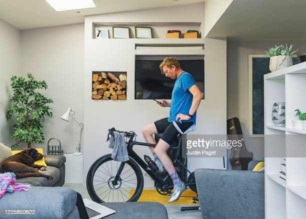 man using his cycling turbo trainer in the living room - shorts stock pictures, royalty-free photos & images