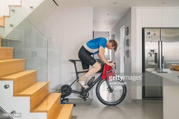 man using his indoor bike turbo trainer at home - indoors stock pictures, royalty-free photos & images