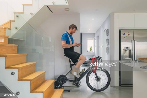 man using his indoor bike turbo trainer at home - peloton stock pictures, royalty-free photos & images