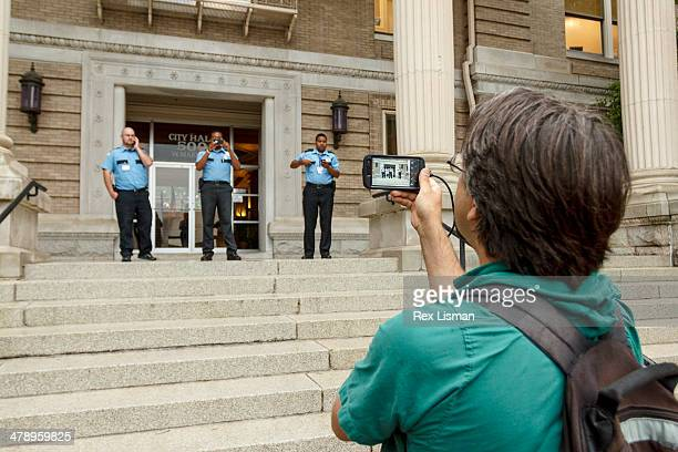 A man using his mobile phone to record video of security guards one of whom is photographing him with a mobile phone during a protest