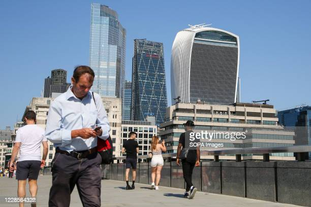 Man using his mobile phone walking while a woman takes photographs on her mobile phone on London Bridge with the skyline of City of London in the...