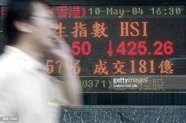 A man using his mobile phone walks past a stock index sign showing the decline in the local stock market in Hong Kong 10 May 2004 Hong Kong shares...