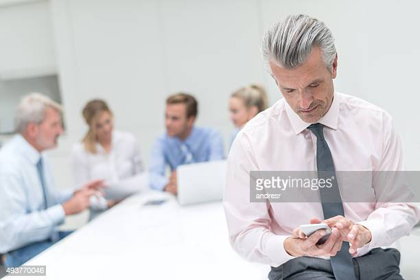 Man using his phone in a business meeting