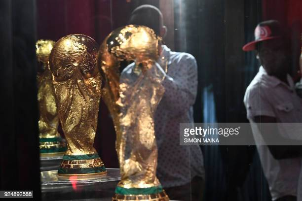 A man using his phone takes a photo of the FIFA World Cup Trophy at the State House in Nairobi on February 27 2018 part of the football...