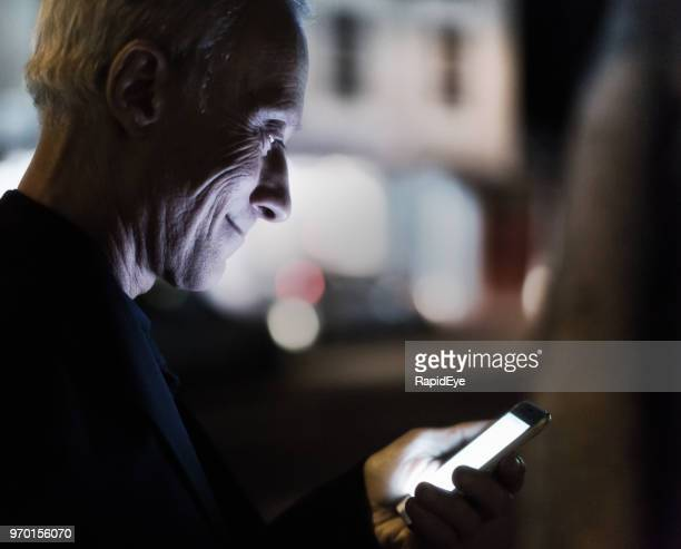man using his smartphone in the street at night - glowing stock pictures, royalty-free photos & images