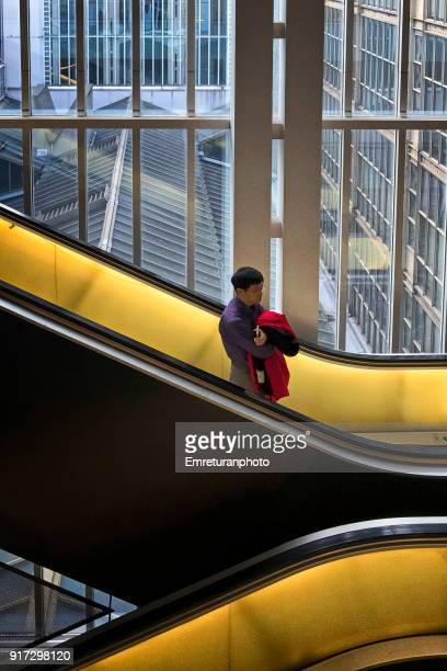 man using illuminated escalator indoors,paris. - emreturanphoto imagens e fotografias de stock