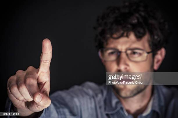 Man using index finger on transparent touch screen