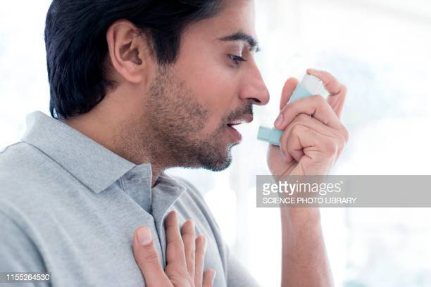 man using inhaler - asthma stock pictures, royalty-free photos & images