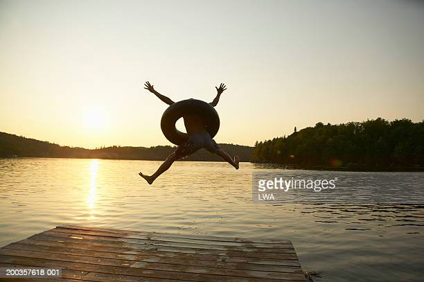 Man using inner tube, jumping from dock into lake, rear view, sunset