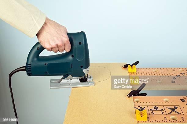 Man using jigsaw to cut semi-circle in hardboard clipped to workbench