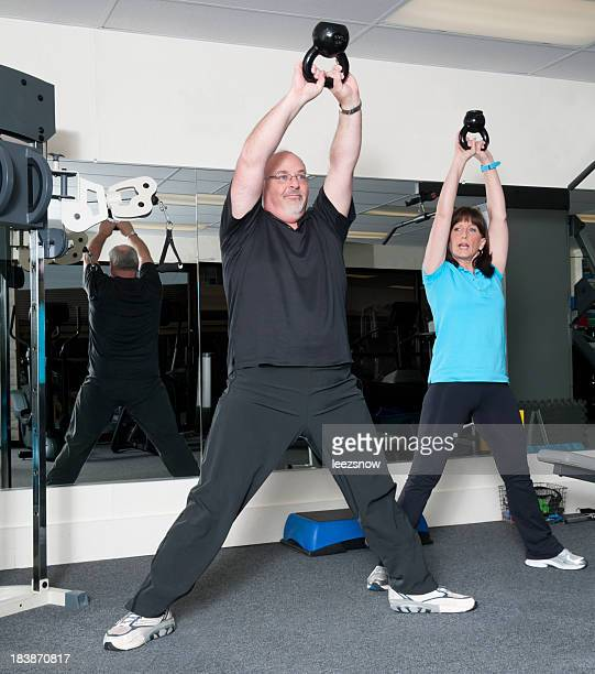 Man Using Kettle Bell Weights With Personal Trainer
