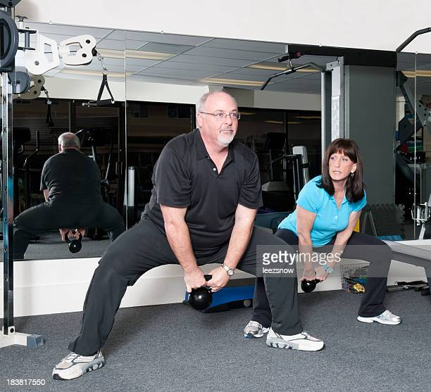 Man Using Kettlebells With Personal Trainer