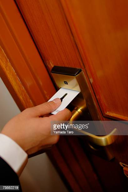 man using key card in door lock - hotel key stock photos and pictures