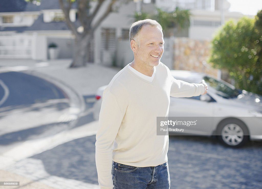 Man using keyless lock on car in driveway : Stock Photo