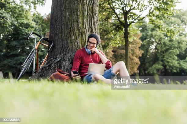 man using laptop and cell phone in park - pedalantrieb stock-fotos und bilder