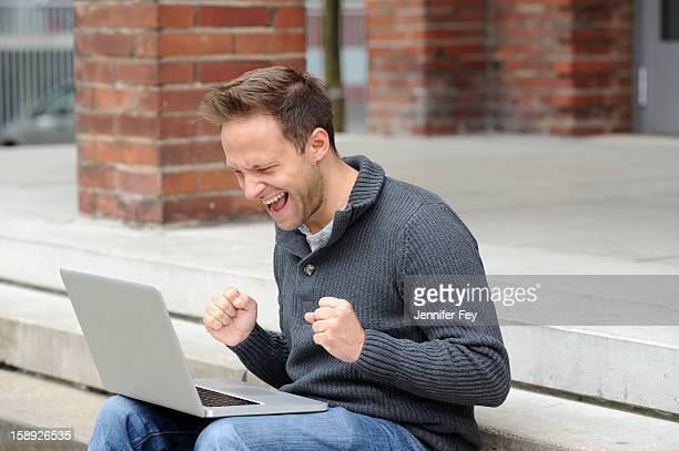 Man using laptop and cheering