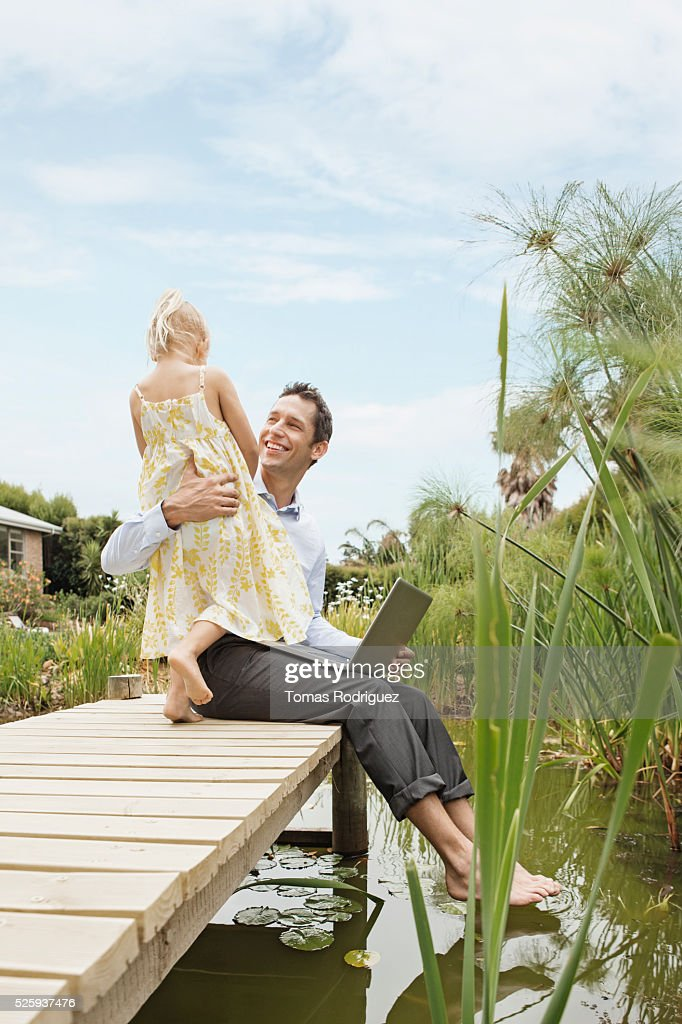Man using laptop and embracing daughter (4-5) on jetty : Stockfoto