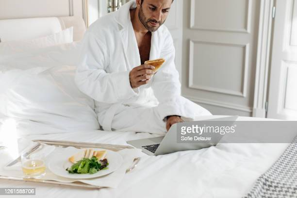 man using laptop and having toast in suite - florence douillet photos et images de collection