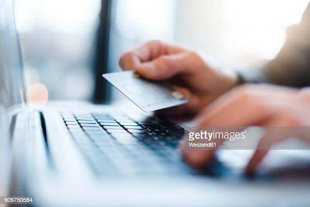 man using laptop and holding credit card, close-up - internet foto e immagini stock