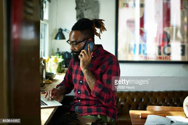 man using laptop and mobile phone in studio. - millennial generation stock pictures, royalty-free photos & images