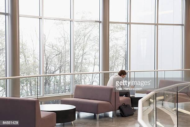 man using laptop and pda in spacious interior - agenda eletrônica - fotografias e filmes do acervo