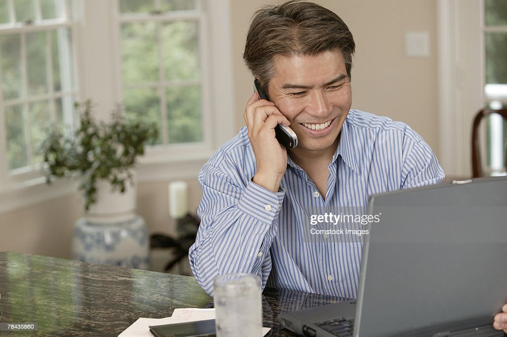 Man using laptop and talking on cell phone : Stock Photo