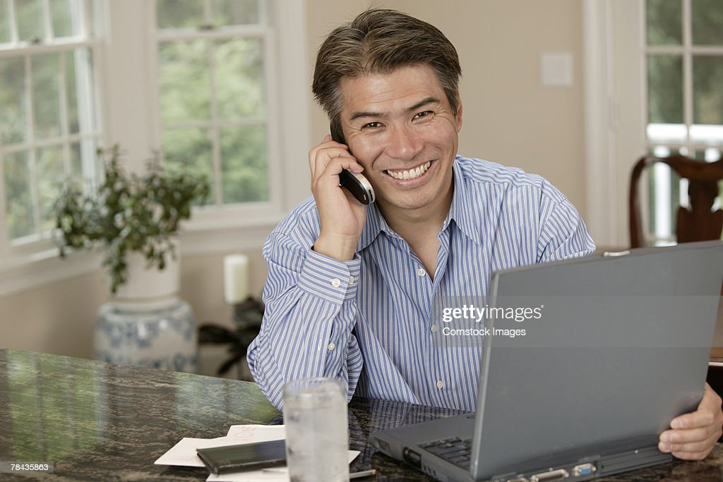 Man using laptop and talking on cell phone : Stockfoto