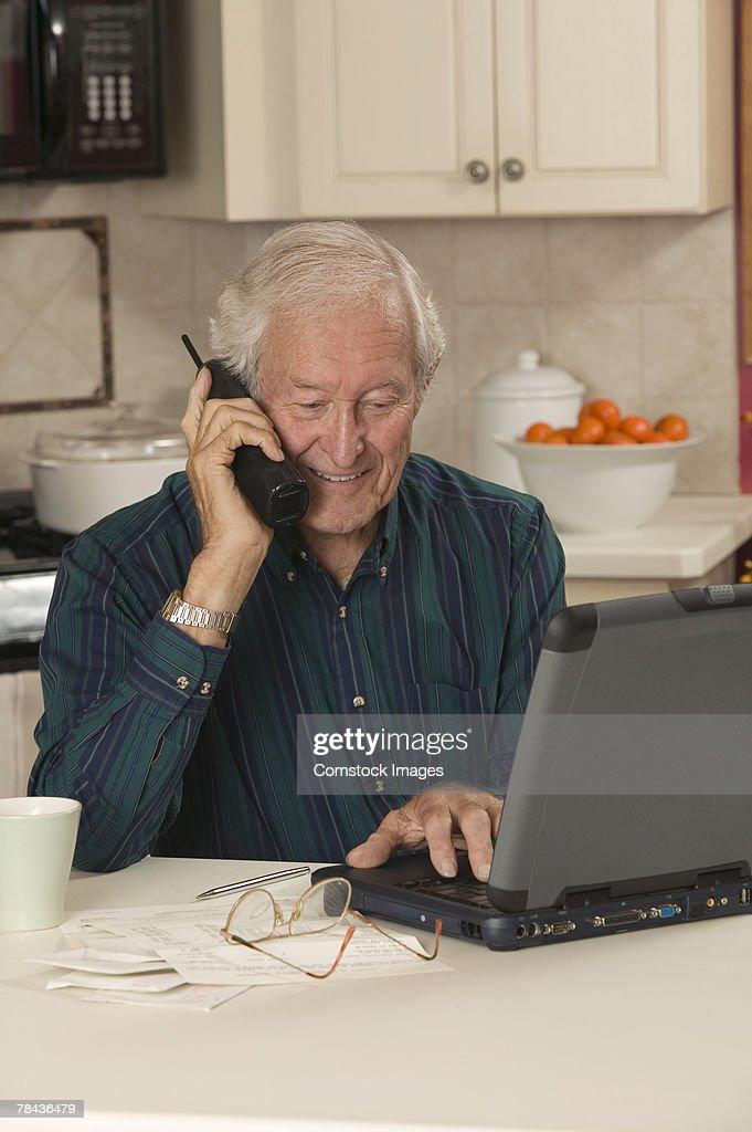 Man using laptop and talking on telephone : Stockfoto