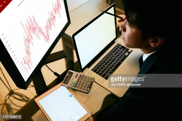 ホームオフィスのデスクでラップトップを使用している男性 - 金融関係の職業 ストックフォトと画像