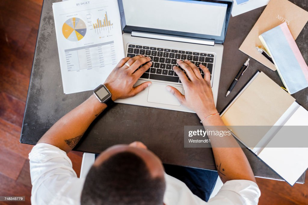 Man using laptop at desk in home office : Stock Photo