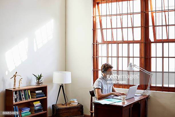 man using laptop at home office - one man only stock pictures, royalty-free photos & images