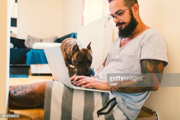 Man using laptop at home with his dog next to him