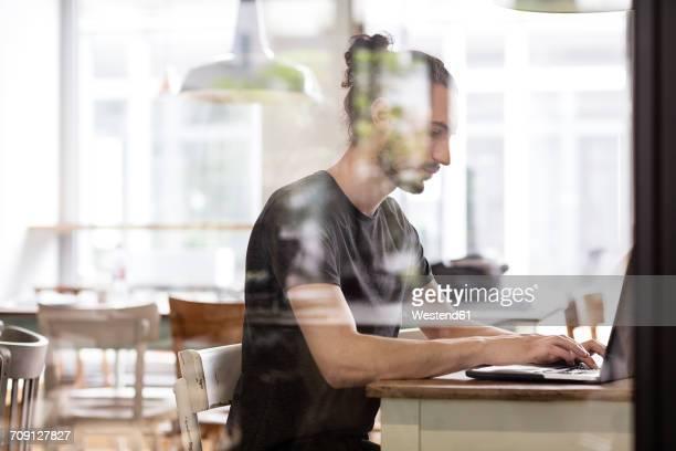 Man using laptop behind glass wall