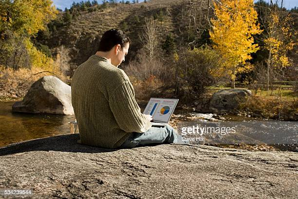 Man Using Laptop by Stream