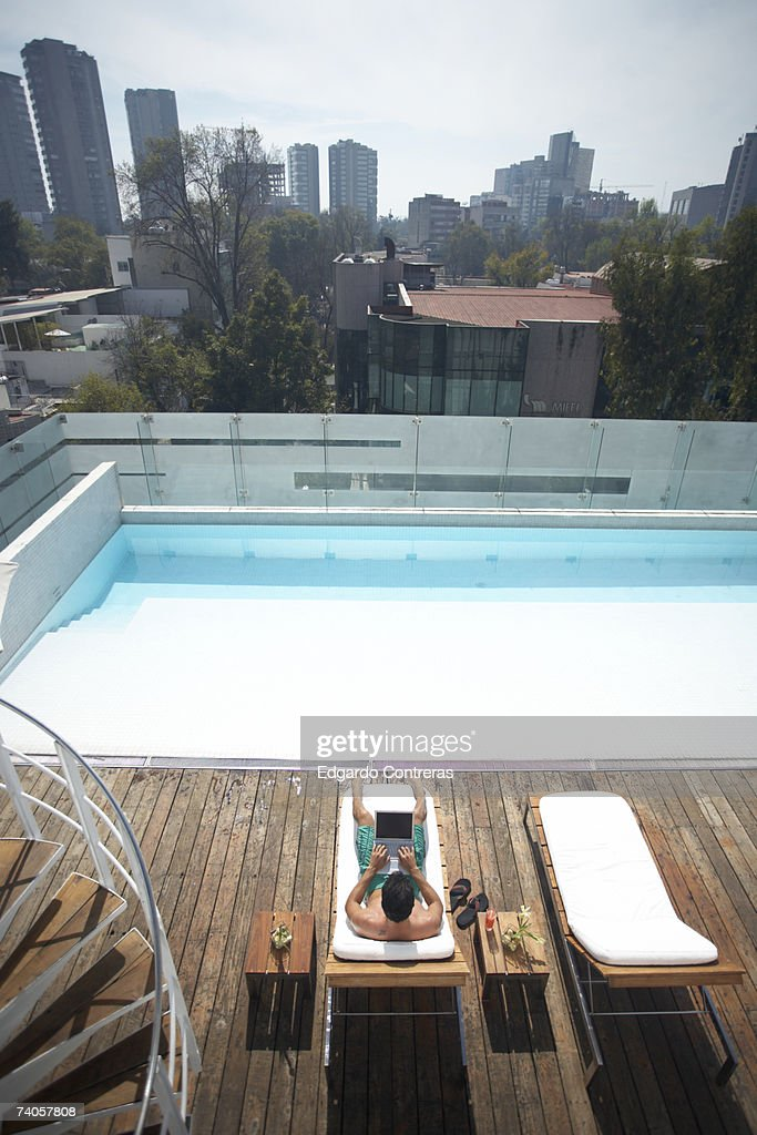 Man using laptop by swimming pool, high angle view : Stock Photo