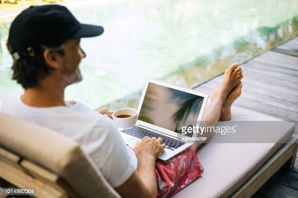 man using laptop computer by the pool - laptop mockup stock photos and pictures