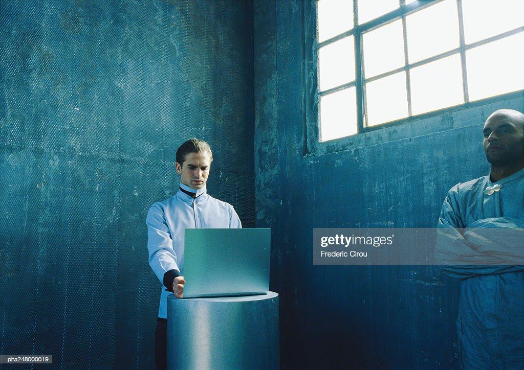 Man using laptop computer, man folding arms : Stockfoto