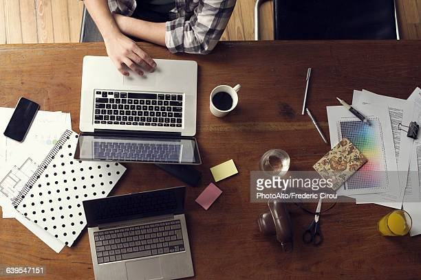 Man using laptop computer on desk cluttered with documents