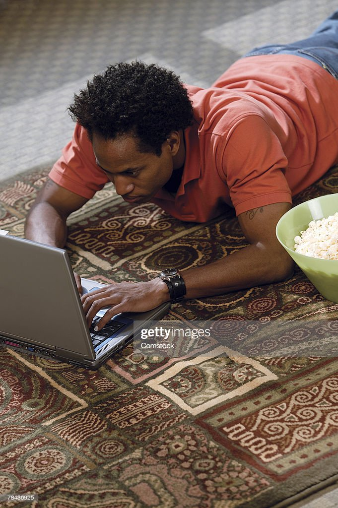 Man using laptop computer on floor of home : Stockfoto