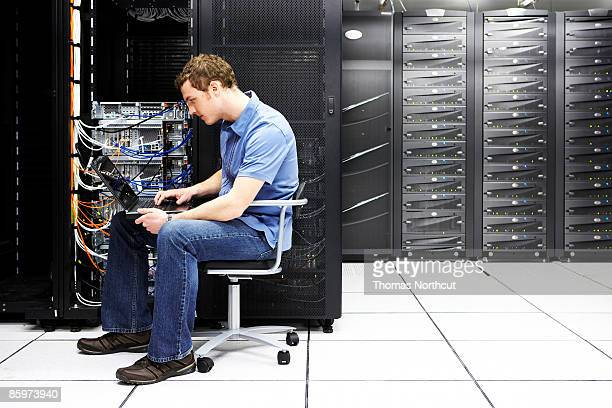 Man using laptop computer, working in server room.