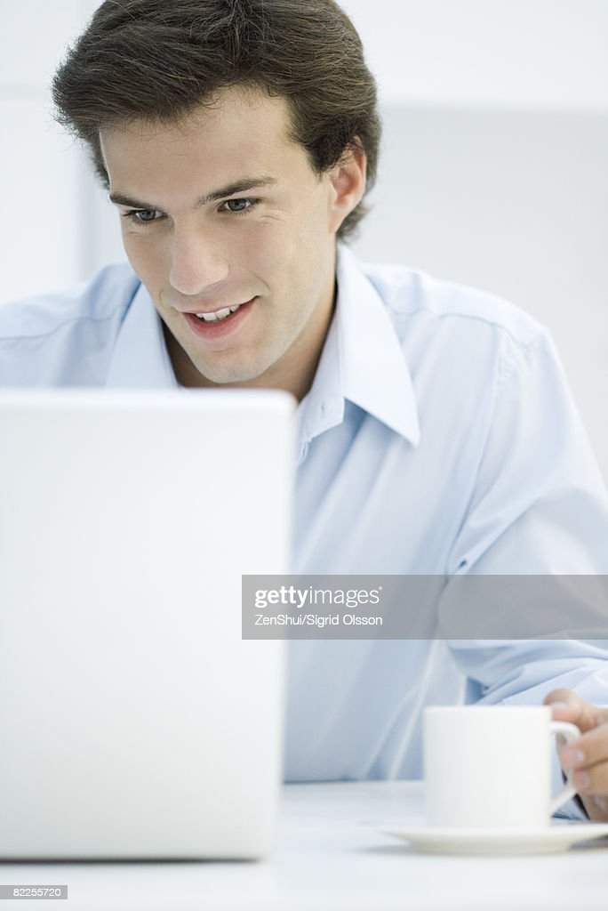 Man using laptop, holding coffee cup : Stock Photo