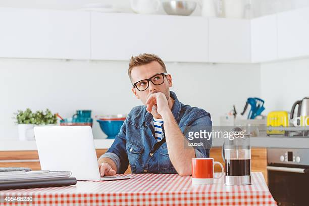 Man using laptop in a domestic kitchen